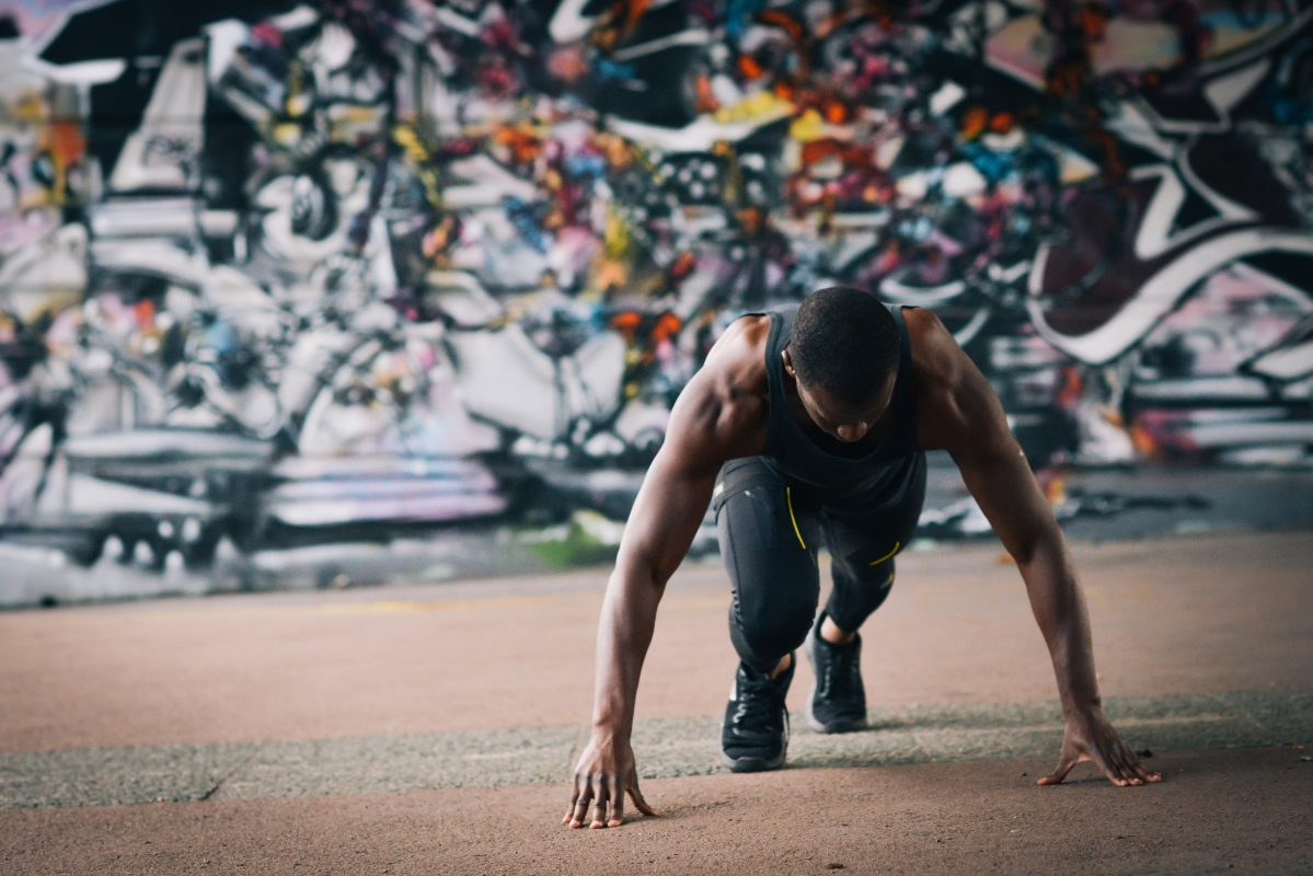 Picture of athlete warming up in HydraForm leggings in front of graffiti-clad wall